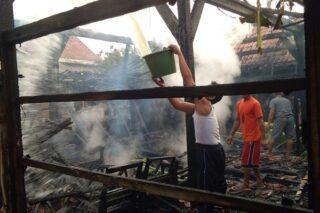 Warga menyiramkan air ke sisa bangunan yang terbakar di Dusun Karangwidoro RT 001/RW 002, Desa Guci, Kecamatan Godong, Kabupaten Grobogan, Sabtu (6/6/2020) sore. (Semarangpos.com-Pemerintah Kecamatan Godong)